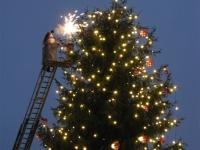 Kerstman steekt de kerstboom aan